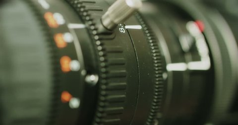 Close-up of a modern TV camera lens -- turning of a zoom and focus rings simultaneously in very shallow depth of field