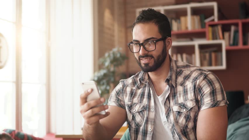 Attractive boy typing on newest mobile, sitting happily in modern comfortable office, wearing stylish checked shirt on usual working day, enjoying technology during coffee break | Shutterstock HD Video #1009589594