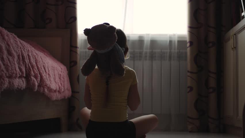 Depressed little girl hugging teddy bear | Shutterstock HD Video #1009597184