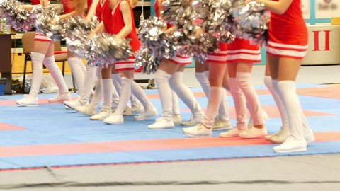 Legs of cheerleaders in red dresses dancing at the karate tornament