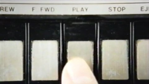 VHS tape capture: pressing play and stop, multiple times, on a vintage player; inserting an audio cassette. Close-up shot.
