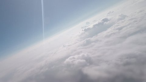 Scenic view from a commercial plane flying above the clouds with beautiful blue sky view and sun rays