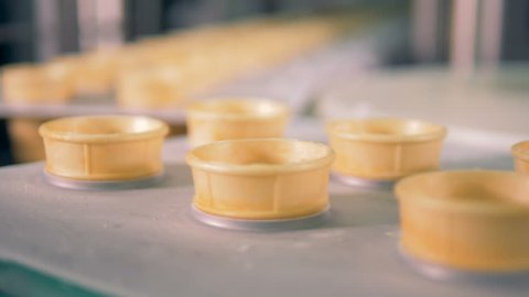 Empty wafer cones moving on conveyor belt at ice-cream factory.