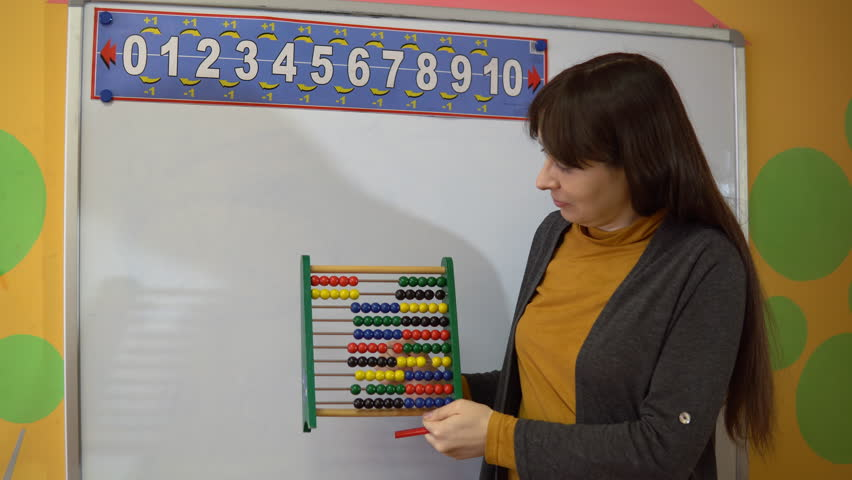 Beautiful young female teacher standing near blackboard in classroom in elementary school, she explains how to use the abacus.
