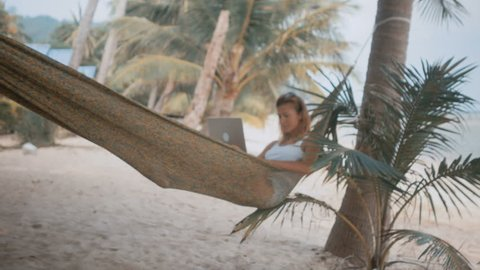 Woman freelancer works on the beach in hammock
