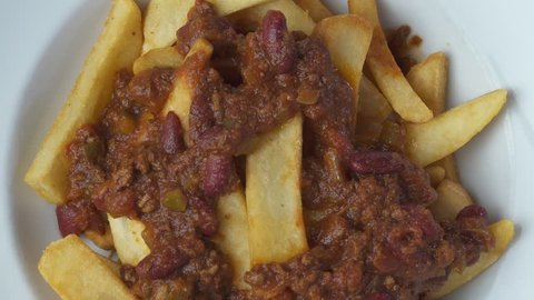 Top view closeup chef's hand putting melted cheese on top of the french fries chips with chilli con carne sauce