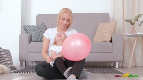 Attractive young blond mom and her charming daughter playing together with pink balloon.