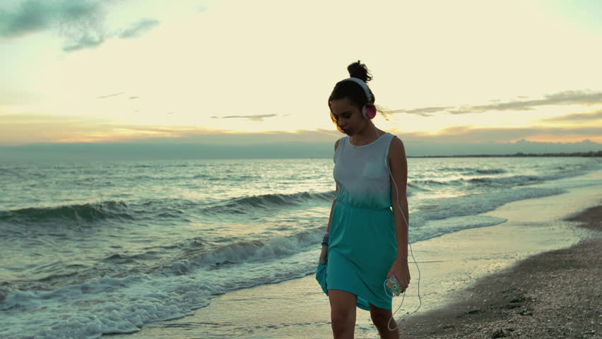 teenager girl with headphones walking on the beach. shot in slow motion #1009694384