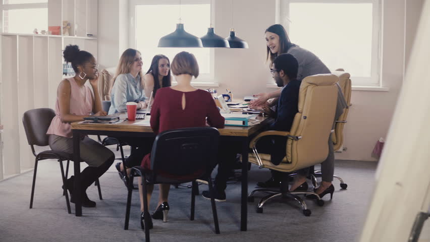 Happy female boss leading office meeting. Multiethnic employees listening to manager instructions in modern coworking 4K | Shutterstock HD Video #1009713194