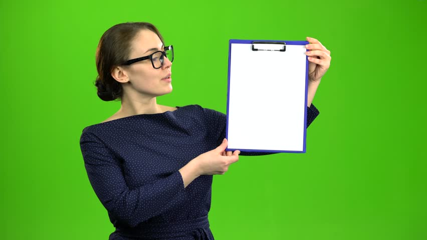 Girl raises a paper tablet and smiles. Green screen