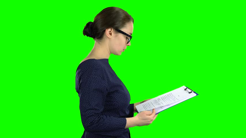 Businesswoman comes with a paper tablet on the street. Green screen. Side view