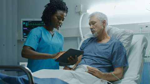 In the Hospital, Senior Patient Lying in the Bed Talking to a Nurse who is Holding Tablet Computer Showing Him Information. In the Technologically Advanced Hospital Ward. Shot on RED EPIC-W 8K Camera.