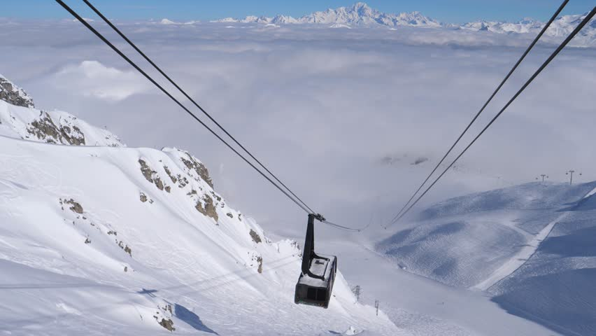 A big cabin ski lifter goes up the snowy mountain on a winter sunny day. Lots of clouds are above mountain peaks on background. 4k, 3840x2160