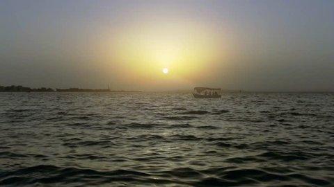 Sunset scene of a felucca (little boat) in the sea (Lake Qaroun, Faiyoum, Egypt)