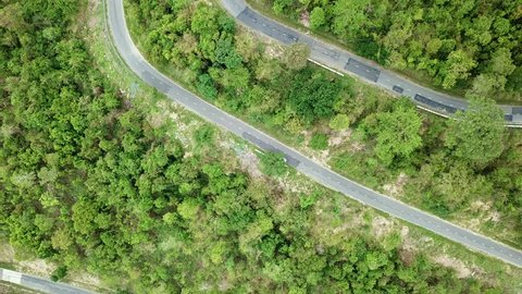 Top view. Aerial view road pass and forest from drone. Royalty high quality free stock video footage of road in forest. Road in forest is beautiful with many tree, road on pass very winding and curve