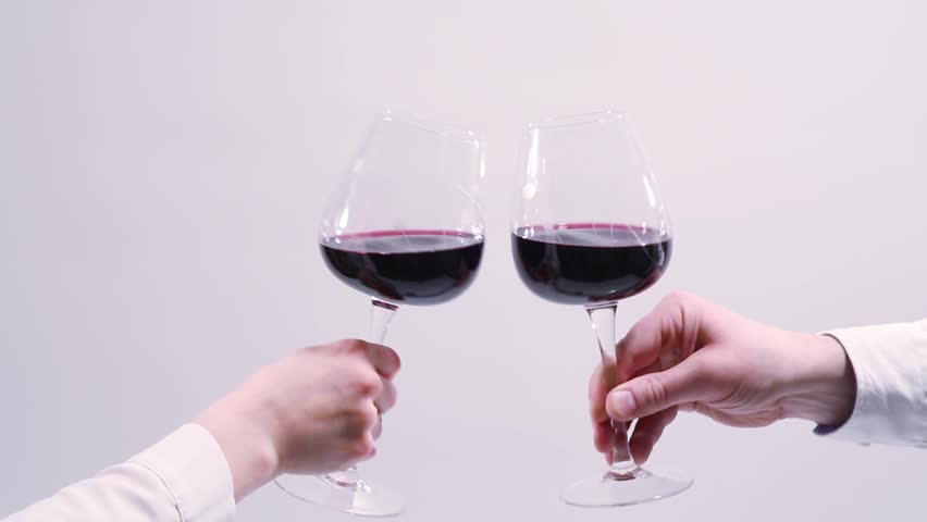 red wine toast, cheers and clinking wine glasses on white background