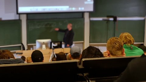 Professor or teacher delivers a lecture college to a large audience of students