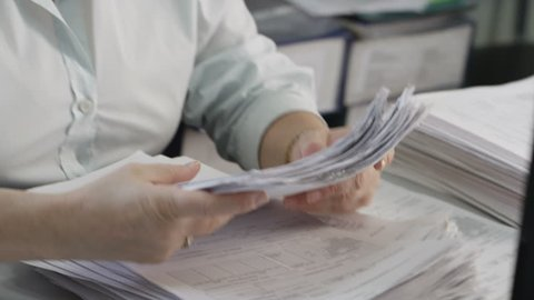 Hands shift a stack of documents