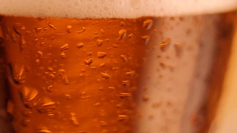 Detail of rotating beer glass with bubbles. Close up beer background.