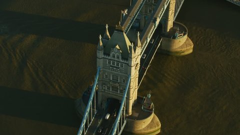 Aerial sunrise view commuter vehicles travelling over Tower Bridge in morning sunlight London England United Kingdom RED WEAPON