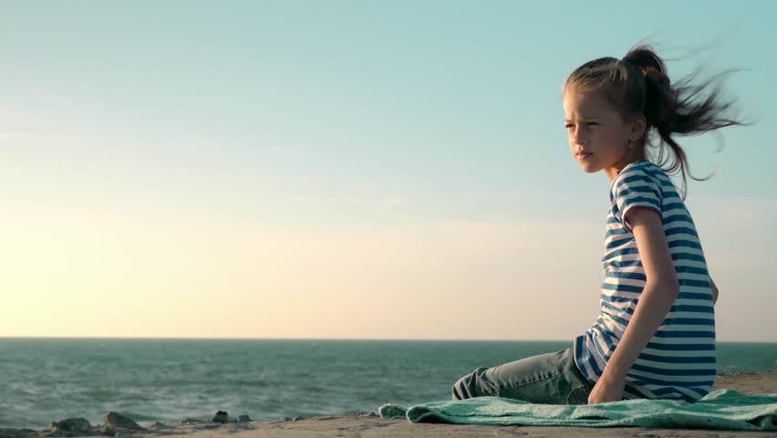 beautiful blonde little girl in a striped t-shirt sits on the beach windy day, copyspace concept health vacation