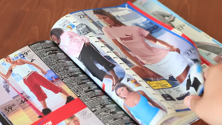 """MOSCOW, RUSSIA, AUGUST 20, 2016: Flipping through the sportswear catalog """"Otto""""."""