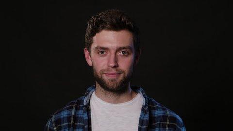 A young man showing a shhh meme against a black background. Close-up shot