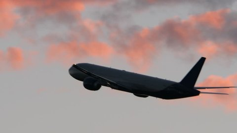 Airplane flying and gaining height in evening cloudy sky