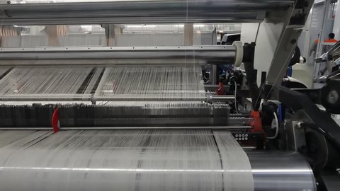 weaving loom at a textile factory, closeup. industrial fabric production line. the camera is stationary