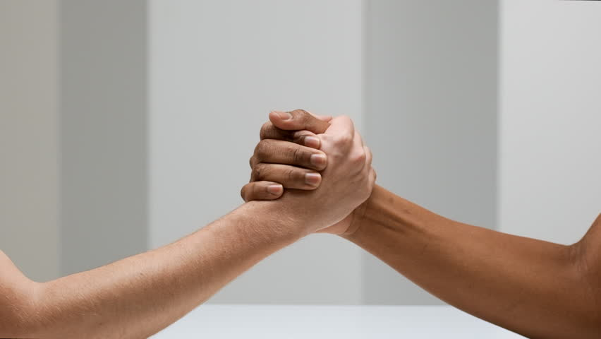 Two hands joining together and doing arm wrestling, isolated over white background in slow motion, competition concept