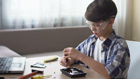 Smart little boy sitting at table and untwisting hard disk drive, IT hobby