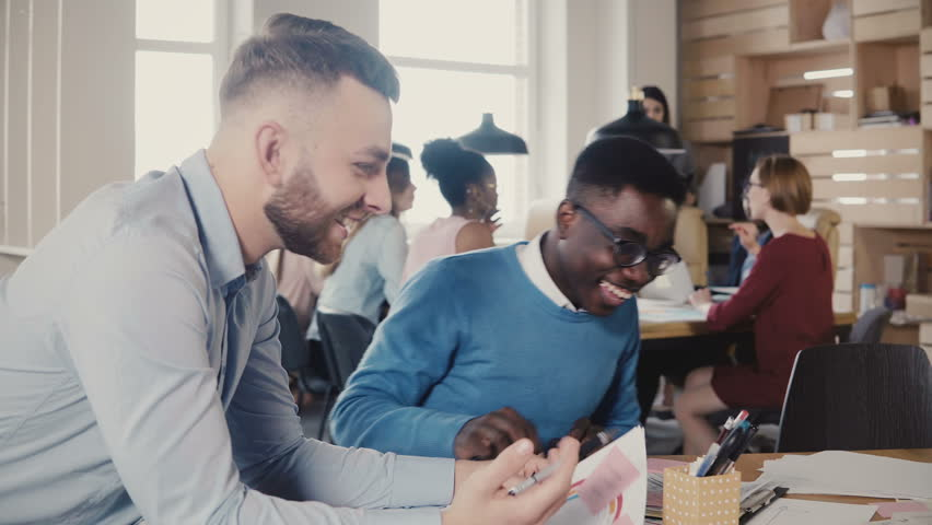 Two mixed race happy young men cooperate on business project in trendy stylish office, laugh, then get focused again 4K. | Shutterstock HD Video #1009815914