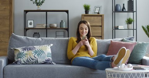 Beautiful young woman in the yellow sweater holding a smartphone in hands and typing on its screen while chatting in the living room at home. Indoors