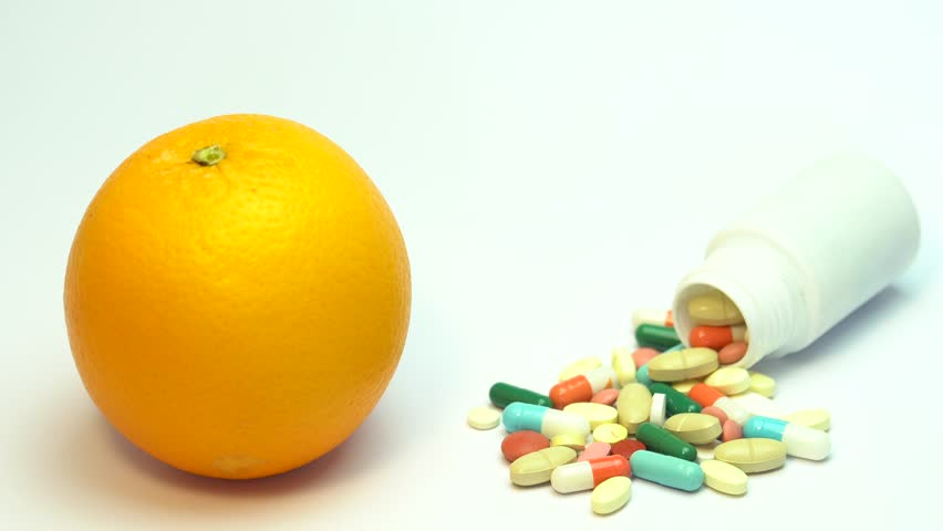 Close up of orange fruit and pills isolated - vitamin concept | Shutterstock HD Video #1009841834