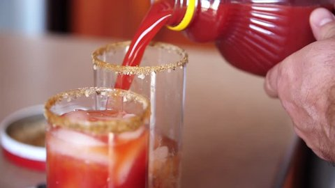 Slow motion shot of pouring tomato juice as an ingredient of a Bloody Mary alcoholic drink.