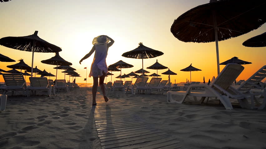 Woman in white dress and hat walk toward camera on beach in the seaside resort with sun loungers and wooden sheds against sunset, cinematic