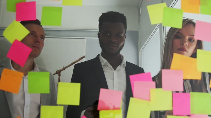 Multi ethnic creative team conducts brainstorming all their ideas are pasted on colored stickers on the glass wall. African American male and blonde team up in the office | Shutterstock HD Video #1009887074