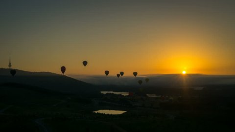 Silhouette time lapse of hot air balloons at sunrise flying high above Canberra, Australia.