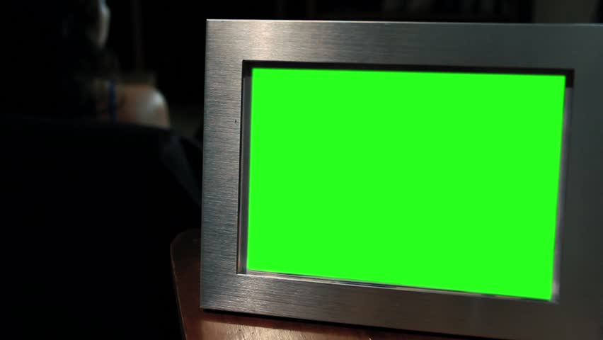 Photo Frame with Green Screen in the Dark. Woman Watching Television On the Background. Zoom Out.