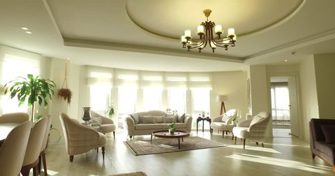 Tracking shot of luxury modern apartment interior design with natural lighting with colorful flowerpot chandelier Persian carpet, candlestick beige sofa ,orchid living room