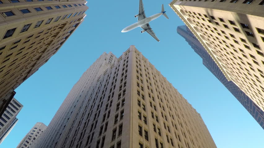 BOTTOM UP, CLOSE UP: Large commercial airplane flies low and close to tall skyscrapers. Breathtaking shot of aeroplane flying over high-rising buildings in business district of metropolitan city.