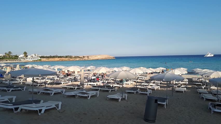 Deckchair or sunbeds with umbrellas on white sand of resort beach. Beach, sea and sky on horizon. Resort vacation on sandy sea beach