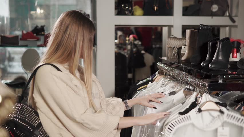A young and pretty woman wants to buy fashionable clothes, a stylist with a backpack on her back examines clothes on a hanger, a lady is in an expensive boutique   Shutterstock HD Video #1009924604