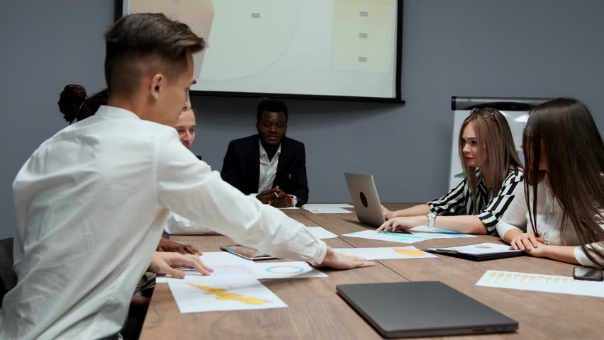 A group of creative multi-ethnic managers disassemble at the meeting of the board of directors in the conference hall the graphs of profit for the last year in the firm. The boss of an African   Shutterstock HD Video #1009936034