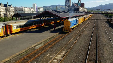 Orange and blue train pulling out from Victorian train station