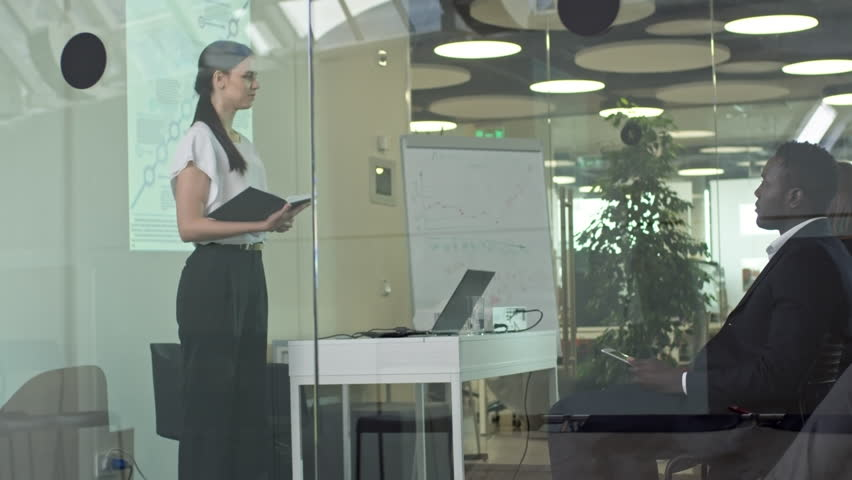 PAN of young businesswoman holding notebook and delivering speech before colleagues in conference room with glass walls   Shutterstock HD Video #1009942664