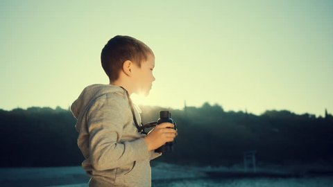 Child looking through binoculars on a summer day at sunset on a sea background