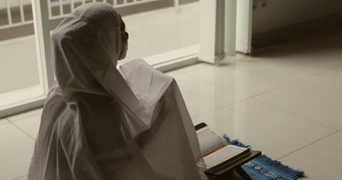 Female muslim worshiping to the GOD after reading Quran while wearing veil at home. Shot in 4k resolution