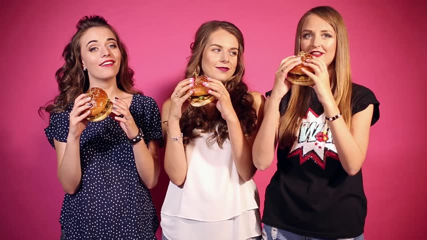 Three young and stylish girls with bright make up and red lips, eating fast food in studio. Cheerful and beautiful models eating big and tasty hamburgers heartily. Pink background.