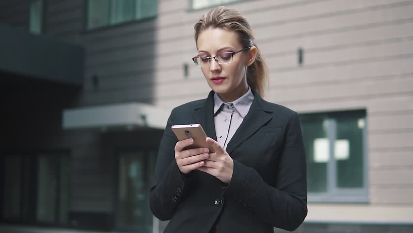The girl in a business suit sends a texting on mobile phone. the wind in your hair   Shutterstock HD Video #1009964474